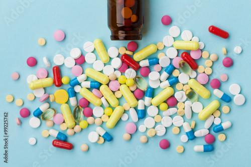 Colorful drug pills on blue background, pharmaceutical concept Plakat