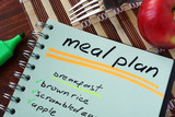 Notepad with meal plan and apple. Diet planning.