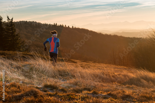 Fototapeta woman running alone in the mountains in the morning