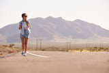 Woman On Vacation Hitchhiking Along Country Road