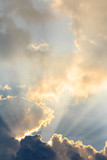Fototapety Clouds and sun beams on evening time