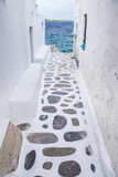 Traditional whitewashed alley of Mykonos with seaview, Greece