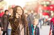 Obrazy na płótnie, fototapety, zdjęcia, fotoobrazy drukowane : Spanish woman talking on the phone with blurred people on backgr
