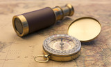Old compass and old telescope on vintage map world explorer concept