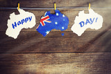 Australia day Concept - greeting written across white Australian maps, kangaroos and koala - hanging pegs (clothespin), 26 January. toned image. sunlight effect