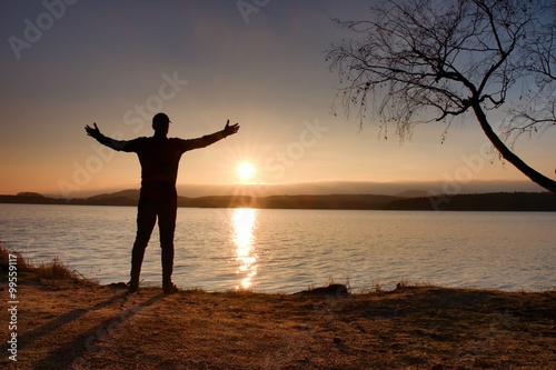 Papiers peints Morning Glory Silhouette of young man stand on beach at sunset. Shadow of active man