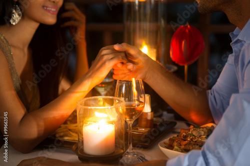 Romantic couple holding hands together over candlelight © luckybusiness