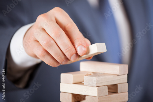 Poster Unrecognizable businessman forming a wooden pyramid