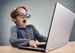 Leinwanddruck Bild - Shocked and surprised boy on the internet with laptop computer