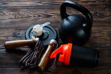 Metal kettlebell, shaker, protein and a jumping rope, closeup