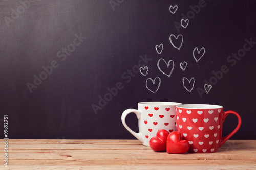 Valentine's day concept with hearts and cups over chalkboard background Poster