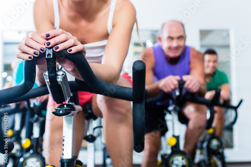 Poster Senior people in gym spinning on fitness bike