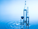Medical ampoules and bottle on blue water background with splash
