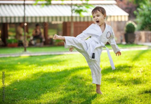 fototapeta na ścianę Preschool boy practicing karate outdoors