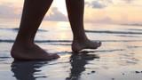 Female Feet Walking Barefoot on Sea Shore at Sunset