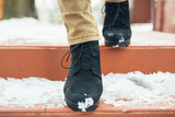 Women's legs in elegant winter boots down the snow-covered stair