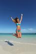 Woman in bikini jumping on beach