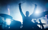Fototapety Drummer playing on drums on music concert. Club lights