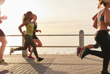 Fototapety Woman running with friends on seaside promenade