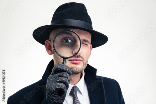 Funny concentrated inspector in black hat looking through the magnifier Poster
