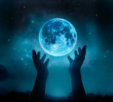 Abstract hands while praying at blue full moon with star in dark background