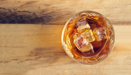 Glass of whiskey with ice on wooden background, Top view