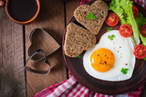 Breakfast on Valentine's Day - fried eggs and bread in the shape of a heart and fresh vegetables. Top view