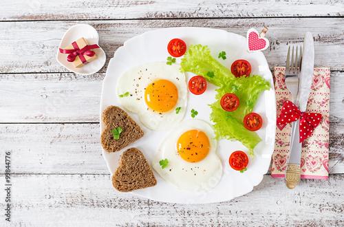 Zdjęcia na płótnie, fototapety na wymiar, obrazy na ścianę : Breakfast on Valentine's Day - fried eggs and bread in the shape of a heart and fresh vegetables. Top view