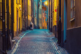The narrow street of Gamla Stan - historic city old center of Stockholm, at summer night, with lanterns