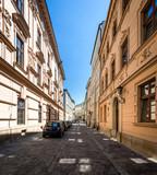 Fototapety Narrow empty street with parked cars in Krakow, Poland.