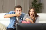 Amazed couple watchi...