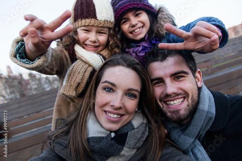 fototapeta na ścianę Happy young family taking a selfie in the street.