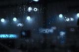 Rain drops on window with street bokeh lights