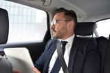 Fototapety Businessman in taxi cab reading news on digital tablet