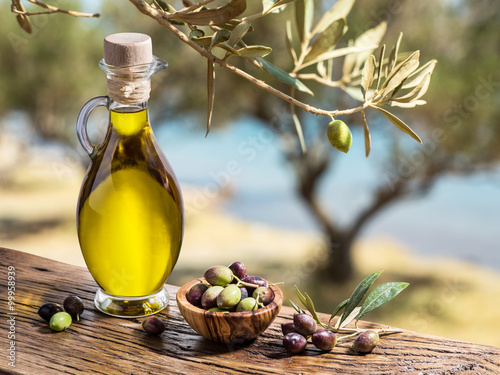 Plagát, Obraz Olive oil and berries are on the wooden table under the olive tr