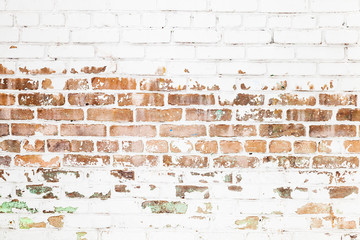 Old red brick wall with damaged white paint layer
