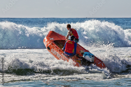 Poster Surf lifesavers guide their dinghy out from the beach into heavy surf