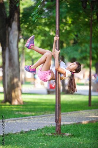 Girl dancer using a street lamp as a gymnastic pole  © Andrey Bandurenko