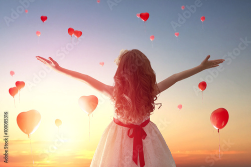 girl looking at red balloons Poster