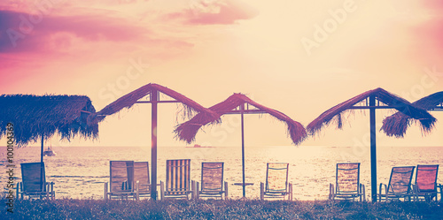 Vintage toned beach chairs and umbrellas at sunset, holidays bac - 100104369