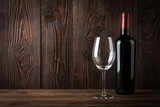 Red wine bottle and wine glass on the dark wooden background