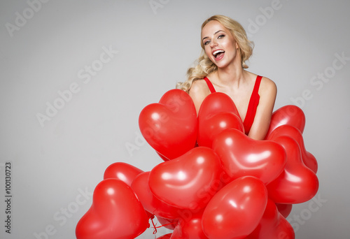 Poster Beautiful smiling blond woman posing on grey background and hold