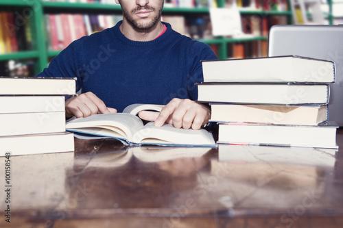 uomo legge libri in biblioteca Poster