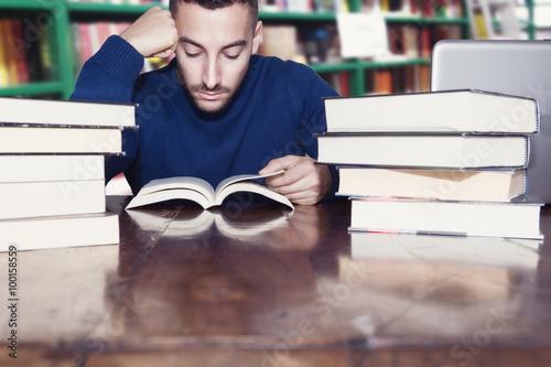 Poster uomo legge libri in biblioteca