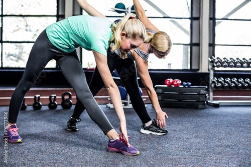 Fototapeta Fit women stretching in the gym