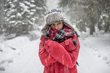 Outdoor portrait of young woman, looking at the camera. Snow covered pine trees on the background. Arms crossed.