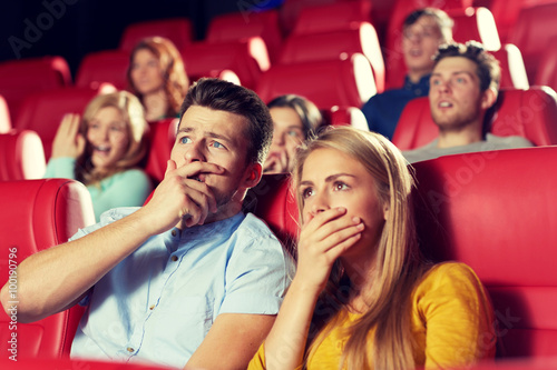 Poster happy friends watching horror movie in theater