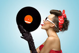 The vinyl desire / A photo of glamorous girl touching vinyl disk with tongue.