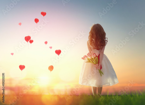 Poster girl looking at red balloons