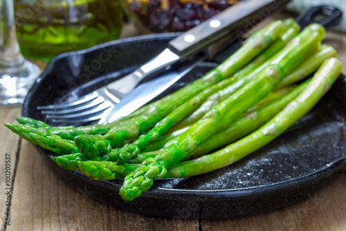 Poster Freshly cooked asparagus appetizer on a cast iron skillet